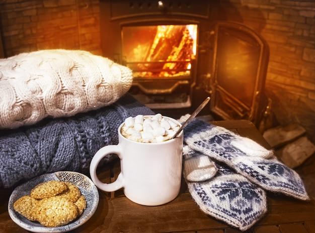 Pile de pulls tricotés confortables, de mitaines faites à la main et d'une tasse de café, de cacao, de chocolat chaud avec des guimauves sur une vieille table en bois, près d'une cheminée en feu.
