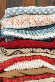 Pile de pulls tricotés de différentes couleurs avec des ornements prêts pour les saisons d'automne et d'hiver