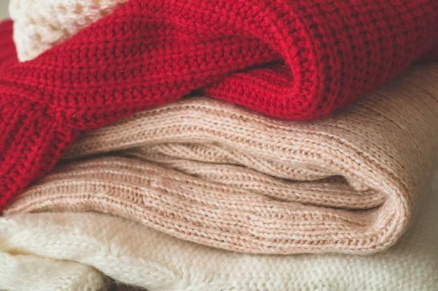 Une pile de pulls tricotés à l'intérieur du salon. le concept du confort automne hiver