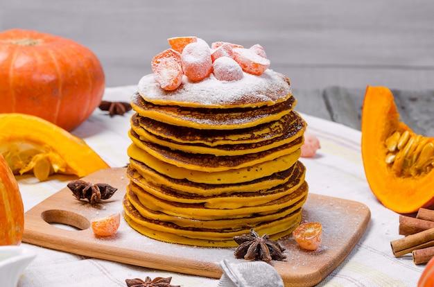 Une pile de punkcakes à la citrouille faits maison avec du sucre en poudre sur le dessus et du kumquat confit.
