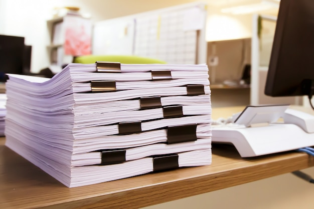 Pile d'un rapport de beaucoup de paperasse ou d'un document imprimé sur le bureau empilé.