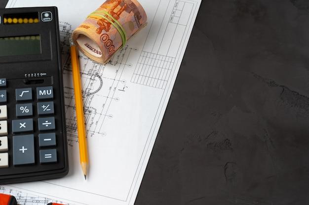 Pile de roubles russes sur plans avec calculatrice. rénovation, concept de dépenses de construction
