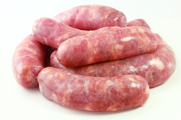 Pile de saucisse de viande de porc crue fraîche isolé sur fond blanc. vue de dessus