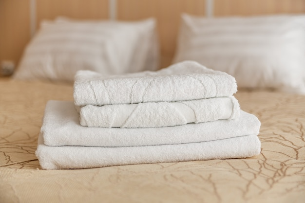 Pile de serviette blanche sur le lit à l'intérieur de la chambre.