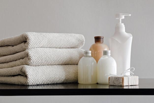 Pile de serviettes, bouteilles avec shampoing, lotion pour le corps, lait de douche et savon à la main sur fond neutre.