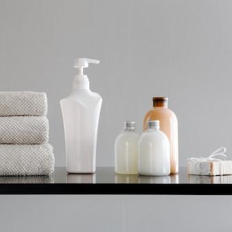 Pile de serviettes, bouteilles avec shampoing, revitalisant, lait de douche et savon artisanal.