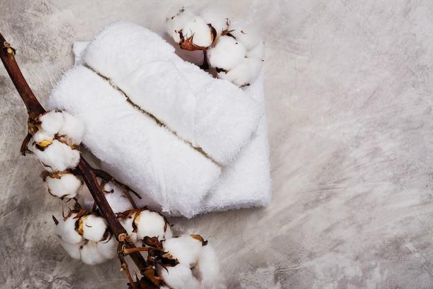 Pile de serviettes en coton, branche avec fleurs en coton, savon et bougie à thé sur pierre grise