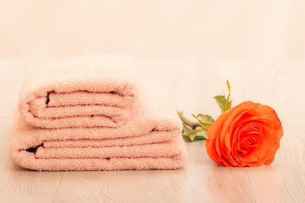 Pile de serviettes éponge douces avec fleur rose rouge sur fond rose.