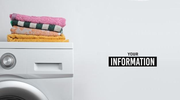 Pile de serviettes sur la machine à laver. fond blanc avec espace copie