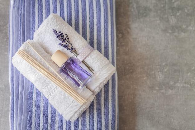 Pile de serviettes propres et douces avec un bouquet de lavande et assainisseur d'air sur gris clair.
