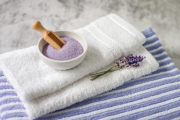 Pile de serviettes propres et douces avec un bouquet de lavande et sel de bain sur gris clair. serviettes de spa contre un mur texturé. minimalisme, flou artistique.