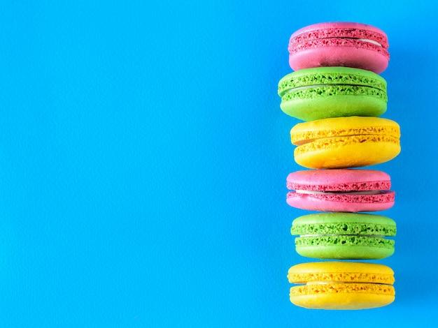 Une pile de six gâteaux de macarons colorés sur fond bleu clair.
