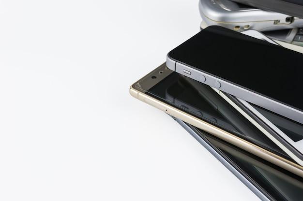 Pile de smartphones haut de gamme sur le bureau blanc.