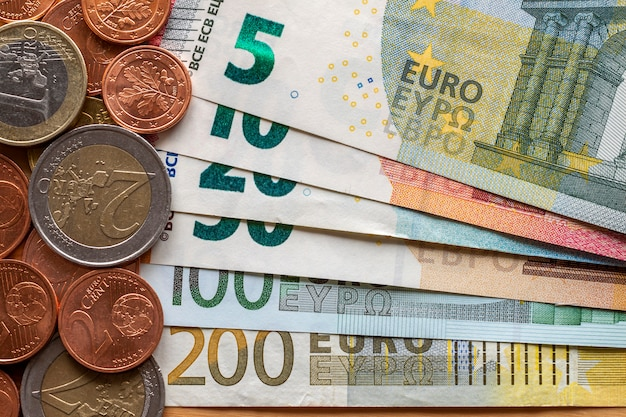 Pile soigneusement rangée de billets en euros, billets de banque d'une valeur de dix, vingt, un et deux cents euros et différentes pièces de métal. argent, affaires et finances, concept d'investissement réussi.
