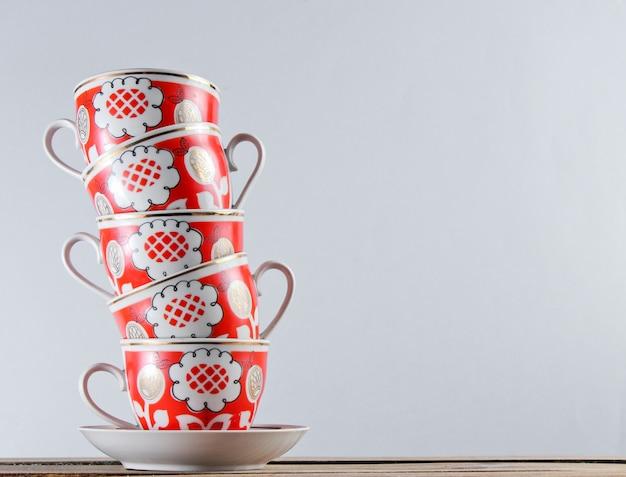 Pile de tasses en céramique antiques sur une table en bois contre un mur blanc