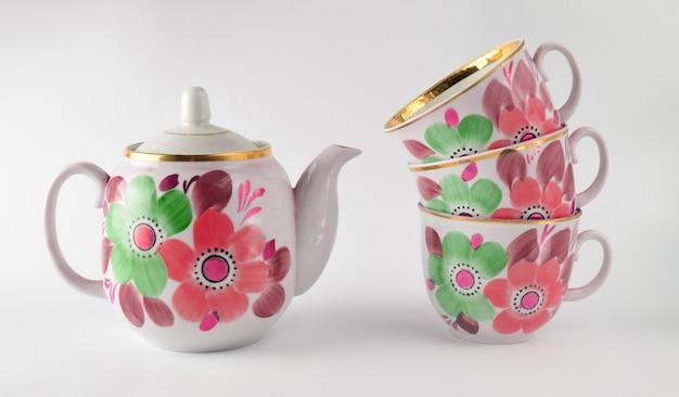 Pile de tasses en céramique antiques, théière sur fond blanc