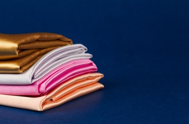 Une pile de tissu satiné multicolore sur fond bleu, espace pour le texte.