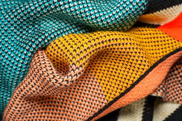 Une pile de tissus colorés fond de formes lisses. tissu en maille multicolore