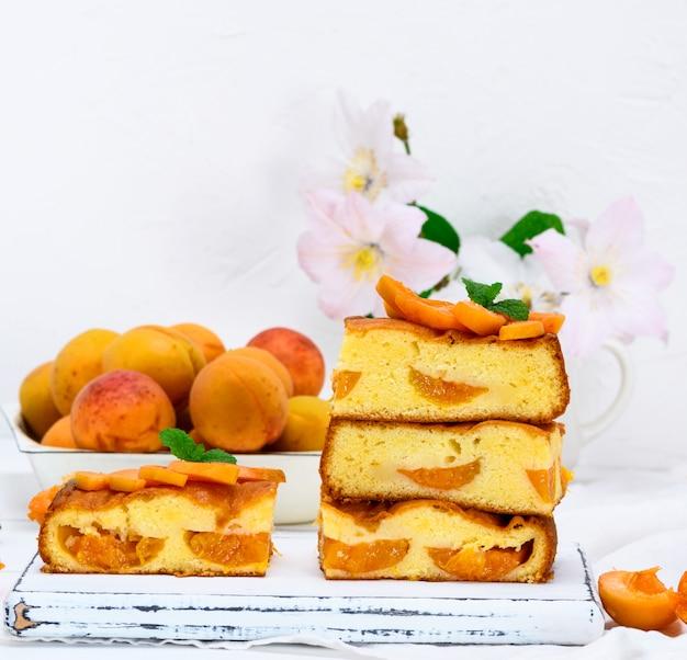 Pile de tranches carrées cuites au four d'une tarte aux biscuits avec des abricots