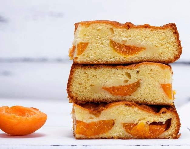 Une pile de tranches carrées cuites au four d'une tarte aux biscuits avec des abricots