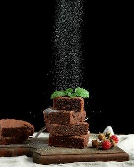 Pile de tranches de gâteau au chocolat brownie cuites au four saupoudrées de sucre blanc