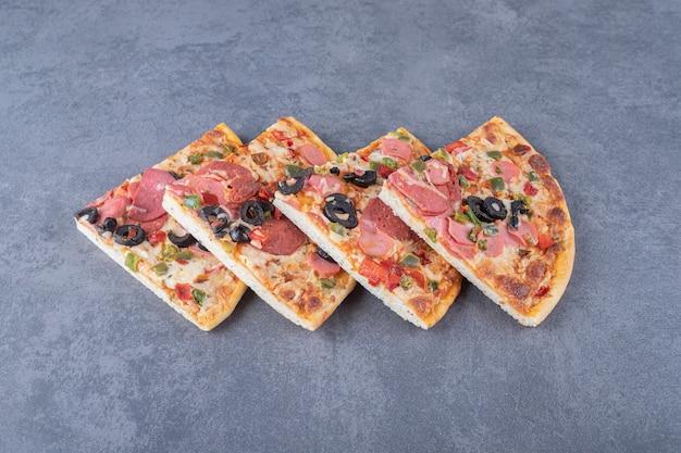 Pile de tranches de pizza au pepperoni sur fond gris.