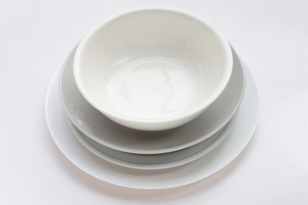 Pile de vaisselle et bol sur fond blanc.