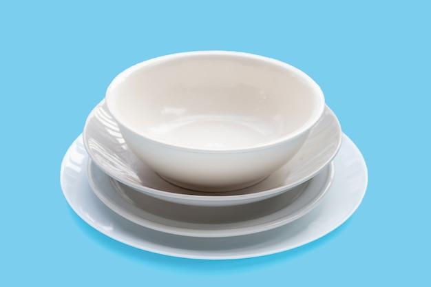 Pile de vaisselle et bol sur fond bleu.