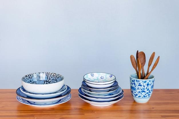Pile de vaisselle en céramique sur une table en bois.