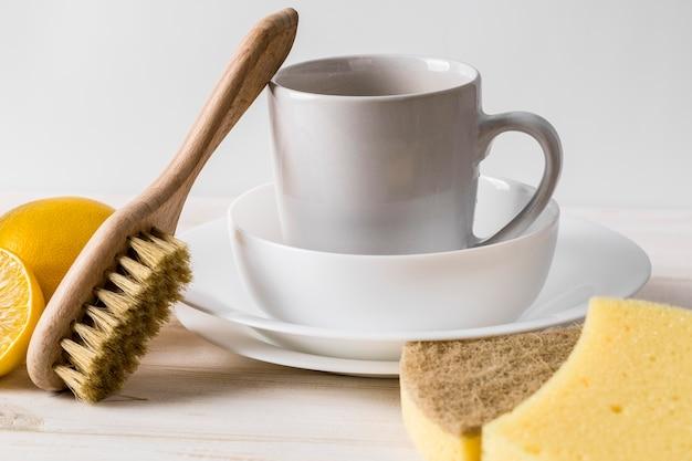 Pile de vaisselle propre et de produits de nettoyage naturels
