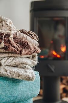Pile de vêtements chauds sur un fauteuil une cheminée en fer