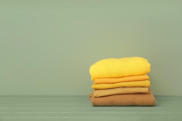 Pile de vêtements chauds sur table contre mur de couleur