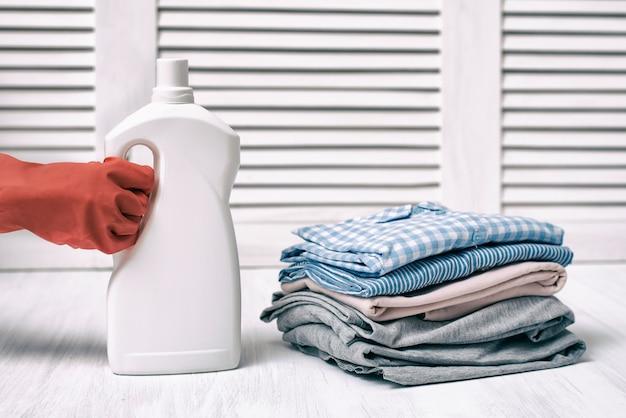 Pile de vêtements pliés et bouteille de détergent à la main féminine. travaux ménagers