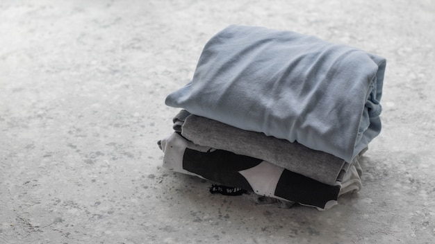 Pile de vêtements pliés sur fond de béton avec espace de copie