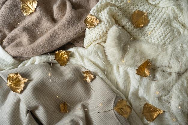 Pile de vêtements tricotés avec des feuilles d'or d'automne espace de tricot de fond chaud pour le texte automne hiver...