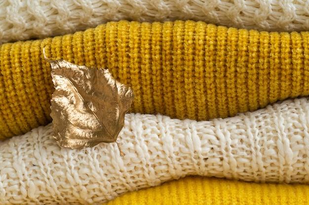 Pile de vêtements tricotés avec des feuilles d'or d'automne