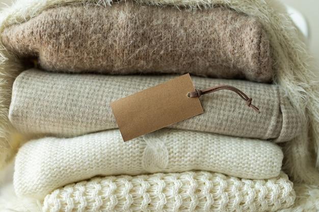 Pile de vêtements tricotés et place d'étiquette vide pour votre texte espace de tricot de fond chaud pour le texte ...