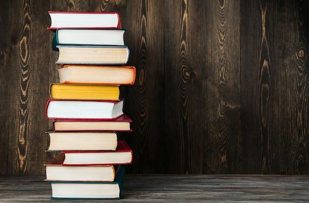Une pile de vieux livres sur un espace de copie de fond en bois.