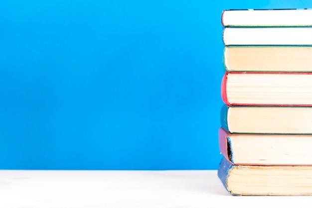 Pile de vieux livres, fond bleu, espace copie. vieux livres cartonnés anciens sur une étagère en bois sur une table de pont, dos non marqué, vide. retour à l'école. éducation