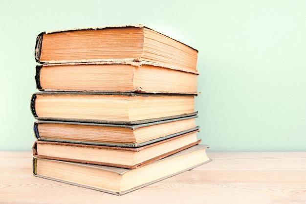 Pile de vieux livres d'occasion sur table en bois et fond bleu pile de vieux livres cartonnés vintage