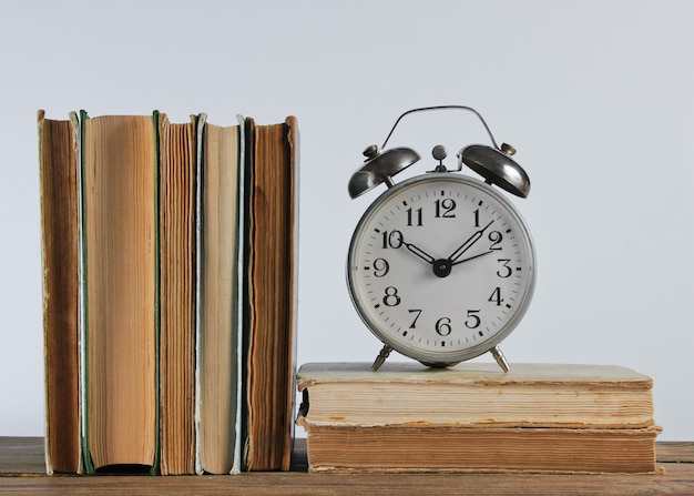 Pile de vieux livres et réveil sur étagère woden contre le mur blanc