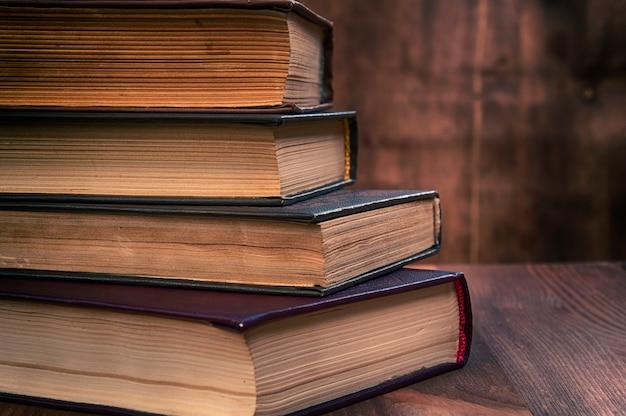 Pile de vieux livres sur une surface en bois marron