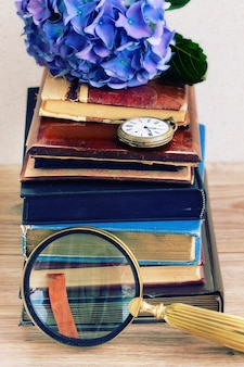 Pile de vieux livres vintage avec des fleurs d'hortenzia bleues et une horloge de poche antique