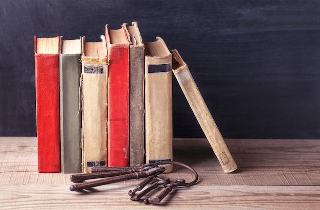Pile de vieux livres vintage et un tas de vieilles clés de fer gros se trouvent sur une table en bois.