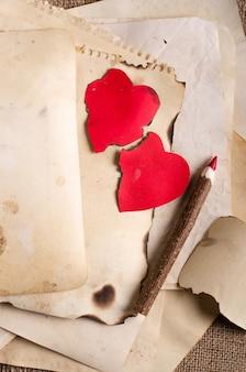 Pile de vieux papiers, cahier, crayon en bois et deux coeurs rouges vintage sur toile de jute, un sac.