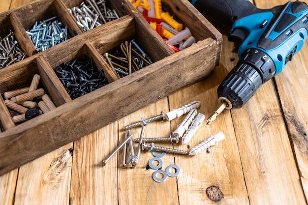 Pile de vis en acier argenté avec boîte en bois et perceuse sans fil.