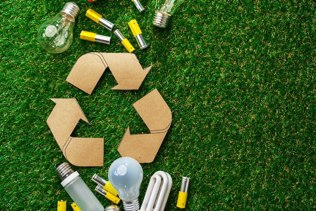 Piles et ampoules alcalines au lithium métal usagées sur la surface de l'herbe