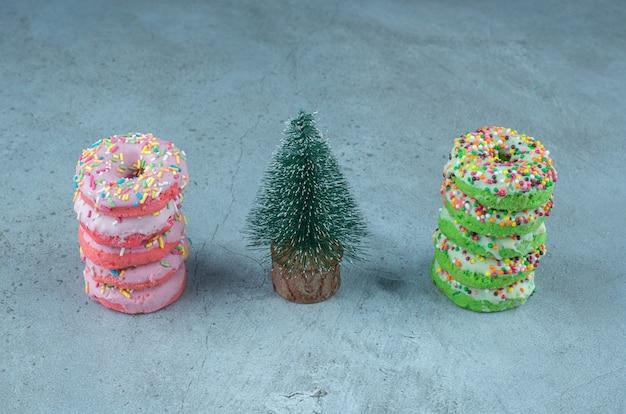 Des piles de beignets et une figurine d'arbre sur marbre.