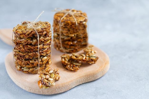 Des piles de bonbons écologiques sains avec différentes graines et miel sur planche de bois