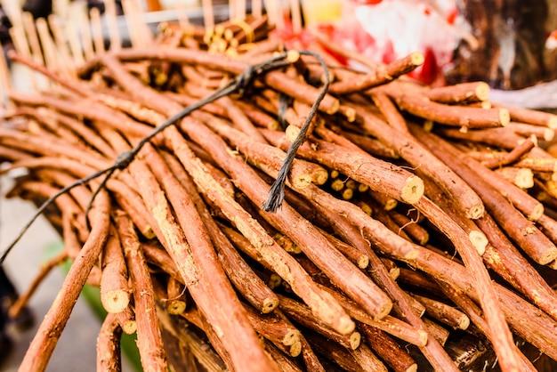 Des piles de branches de réglisse séchées à vendre.